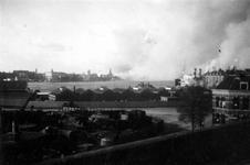 XXXIII-569-37-33 Gezicht op het brandend en rokend Rotterdam, de noordelijke oever van de Nieuwe Maas ter hoogte van de ...