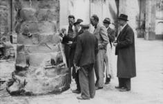 XXXIII-574-00-03-4 Leden van een commissie van deskundigen onderzoeken de zwaar beschadigde Sint-Laurenskerk.