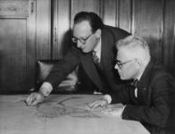 XXXIII-574-01-2 Ir. W.G. Witteveen (links) aan wie de opbouw van de nieuwe binnenstad is opgedragen, geeft burgemeester ...