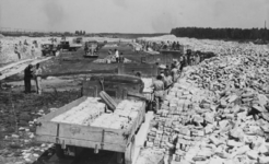 XXXIII-574-4 Afgebikte stenen uit de verwoeste binnenstad zijn opgestapeld langs de Soetendaalseweg.