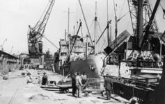 XXXIII-667-1 Het overladen van Engels voedsel (kaakblikken) van een zeeschip naar een binnenvaartschip.