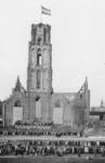 XXXIII-680 Opvoering van het bevrijdingsspel op een podium voor de Sint-Laurenskerk. Rechts op de achtergrond: de molen ...
