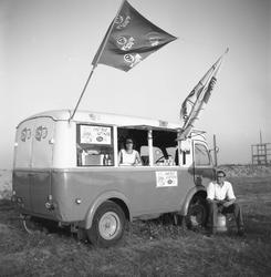12-01 Een ijswagen met Ola IJsvlaggen in de Botlek of op de Maasvlakte. De personen in en voor de ijskar zijn Rudi ...