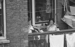 13-01 Twee dames drinken koffie en roken een sigaret op een balkon van een woning aan de Cronjéstraat.