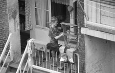 13-02 Een dame hangt de was op aan een kleine warande van een woning aan de Cronjéstraat.